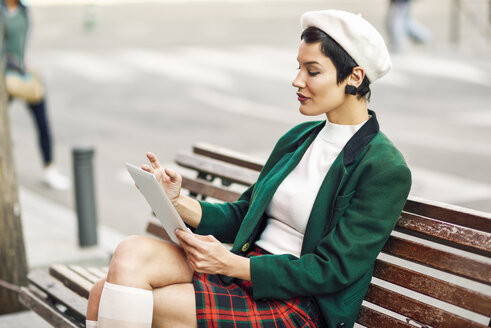 Fashionable young woman sitting on a bench using tablet - JSMF01000