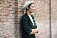 Fashionable young woman wearing a beret and a green jacket at a brick wall - JSMF01003