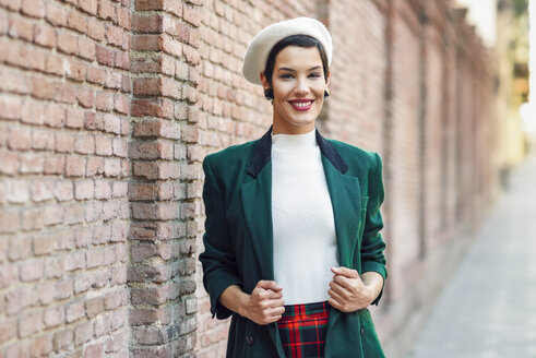 Portrait of smiling fashionable young woman at a brick wall - JSMF01006