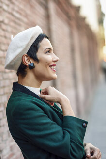 Happy fashionable young woman wearing a beret and a green jacket at a brick wall - JSMF01009