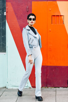 Spain, Madrid, Madrid. Modern woman with short hair, wearing light blue jumpsuit, leather jacket and sunglasses with colorful urban background. Fashion concept. - JSMF01012