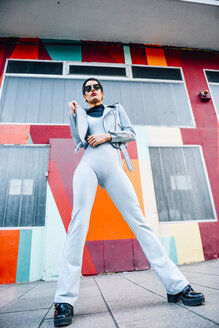 Spain, Madrid, Madrid. Modern woman with short hair, wearing light blue jumpsuit, leather jacket and sunglasses with colorful urban background. Fashion concept. - JSMF01018