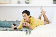 Young woman using cell phone in bed - JSMF01030