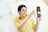 Smiling young woman using cell phone in bed - JSMF01033