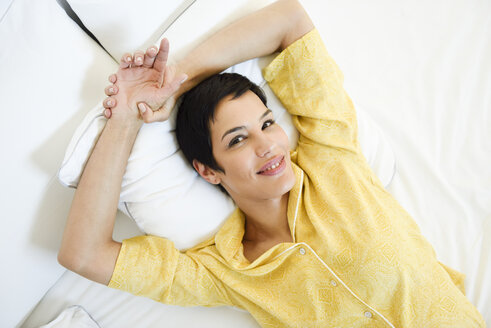 Portrait of smiling young woman lying in bed - JSMF01036