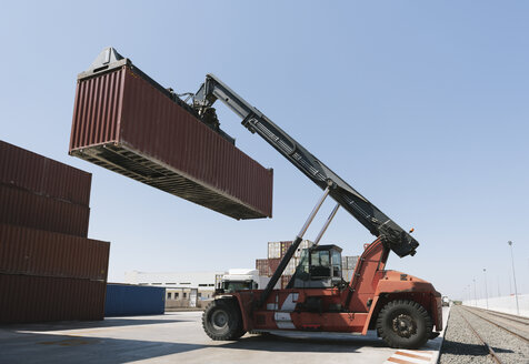 Crane lifting cargo container near railway tracks on industrial site - AHSF00166