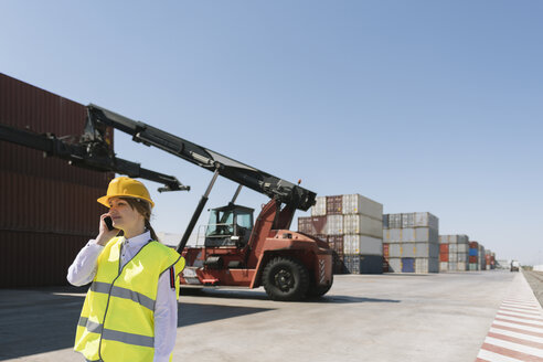 Female worker on the phone in front of crane with cargo container on industrial site - AHSF00172