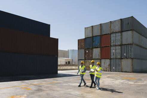 Workers walking together near stack of cargo containers on industrial site - AHSF00193