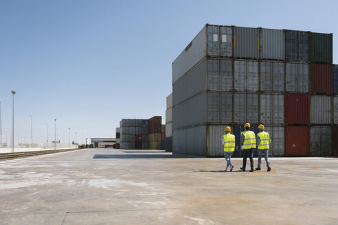Workers walking together near stack of cargo containers on industrial site - AHSF00196