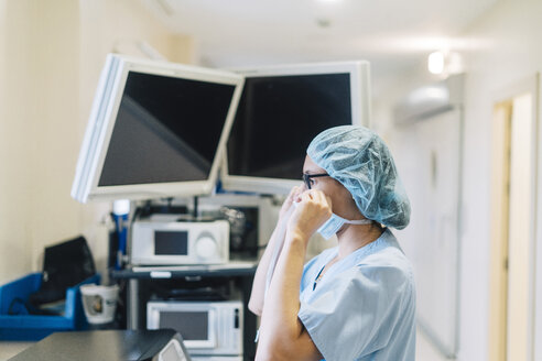 Unrecognizable doctor covering his face with mask at the hospital. Medical concept - JCMF00047