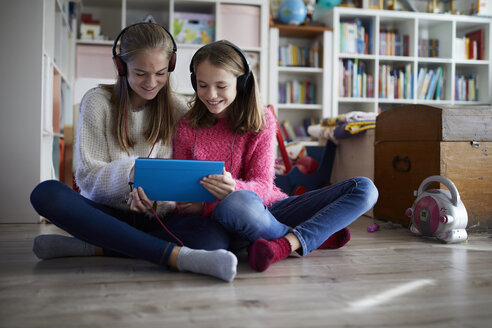 Siblings playing at home with their digital tablets, sitting on ground - RBF07017