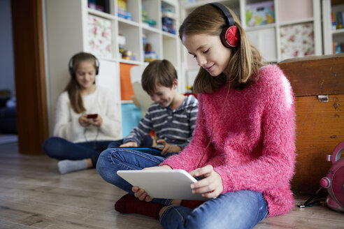Siblings playing at home with their digital tablets, sitting on ground - RBF07020