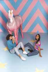 Young woman taking a picture of her friend at an indoor theme park with a unicorn figure - AFVF02809