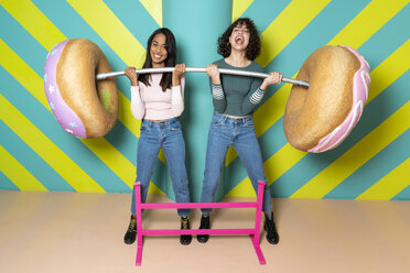 Two happy young women at an indoor theme park having fun with oversized donuts - AFVF02815