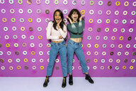 Two young women screaming at an indoor theme park with donuts at the wall - AFVF02818