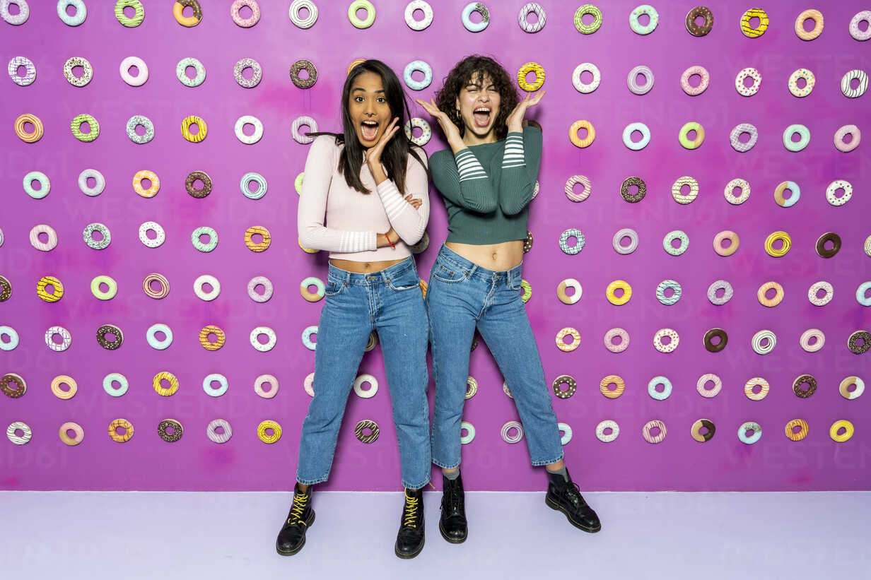 Two young women screaming at an indoor theme park with donuts at the wall - AFVF02818 - VITTA GALLERY/Westend61