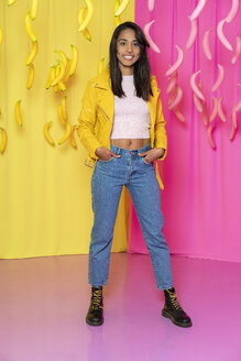 Portrait of a young woman at an indoor theme park with dangling pink and yellow bananas - AFVF02824