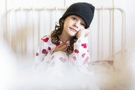 Portrait of little girl sitting in bed wearing cap and pyjama - ERRF01187