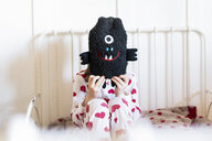 Little girl sitting in bed hiding face behind her soft toy - ERRF01193