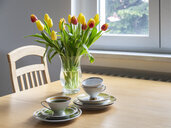 Bouquet of red and yellow tulips on dining table with coffee cups - MELF00206