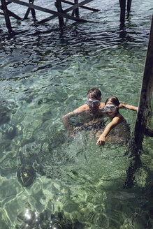 Indonesia, Komodo National Park, father and daughter with diving goggles in the sea - MCF00125