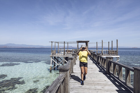 Indonesia, Komodo National Park, girl on a jetty taking a picture - MCF00128
