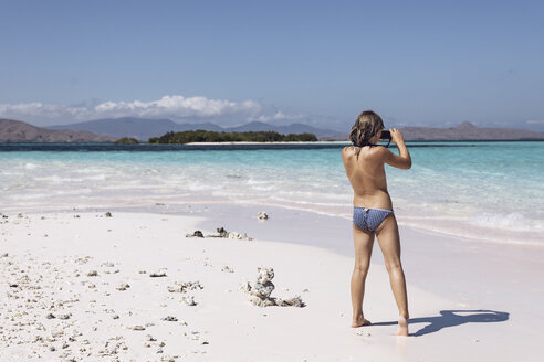 Indonesia, Komodo National Park, girl on beach taking a picture - MCF00137