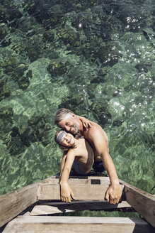 Indonesia, Komodo National Park, happy father and daughter hugging in the sea - MCF00140