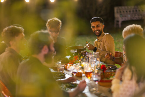 Happy friends enjoying dinner garden party - CAIF23207