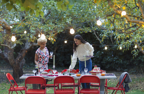 Women friends setting table for dinner garden party - CAIF23222