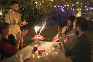 Happy friends celebrating birthday with sparkler cake at garden party table - CAIF23225