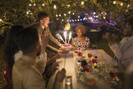 Happy friends celebrating birthday with sparkler cake at garden party table - CAIF23228