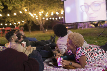 Friends relaxing, watching movie on projection screen in backyard - CAIF23240