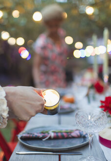 Woman lighting candles for dinner garden party - CAIF23246