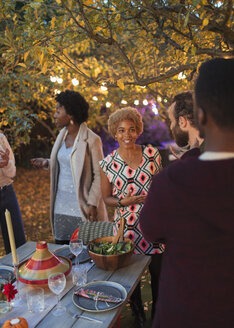 Friends talking at dinner garden party - CAIF23258