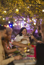 Friends toasting wine glasses, enjoying dinner garden party - CAIF23267