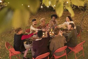 Friends toasting wine, enjoying dinner garden party - CAIF23270