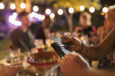 Woman paying for dinner with smart card on patio - CAIF23273
