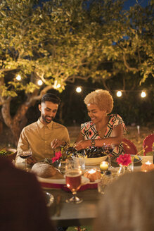 Couple enjoying dinner garden party - CAIF23276