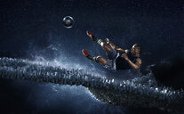 Male soccer player kicking soccer ball against futuristic background - CAIF23291