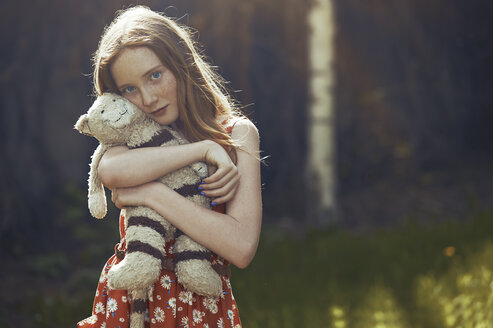 Portrait serene tween girl with stuffed animal in park - CAIF23318