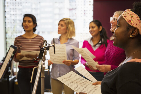 Womens choir with sheet music singing in music recording studio - CAIF23340