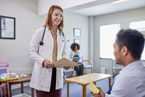 Female doctor talking with male patient in clinic waiting room - CAIF23376