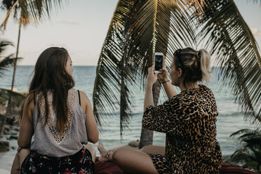 Mexico, Quintana Roo, Tulum, two young women with cell phone relaxing on the beach - LHPF00664