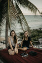 Mexico, Quintana Roo, Tulum, two happy young women relaxing on the beach - LHPF00667