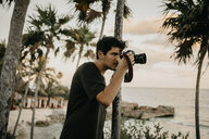 Mexico, Quintana Roo, Tulum, young man taking pictures on the beach - LHPF00670