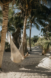 Mexico, Quintana Roo, Tulum, young woman lying in hammock on the beach - LHPF00676