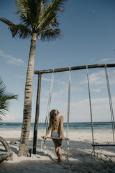 Mexico, Quintana Roo, Tulum, young woman on a swing on the beach - LHPF00679