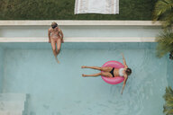 Two young women relaxing in swimming pool - LHPF00682