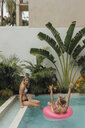 Two happy young women relaxing in swimming pool - LHPF00685